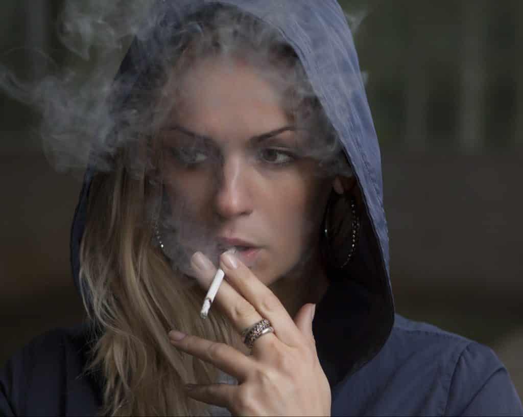 Frau raucht Zigarette und schaut in die Gegend